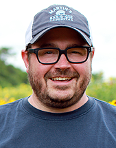 headshot of chef Sean Brock, standing in a field